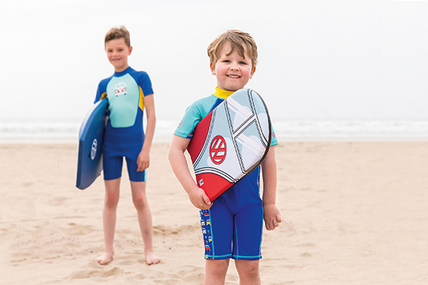 Two children standing on a beach holding VW bodyboards