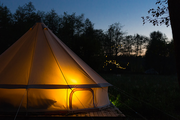 A bell tent at night illuminated from the inside