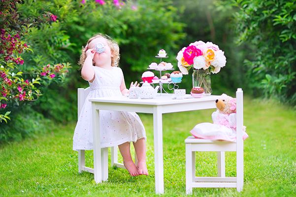 A young girl sitting a table drinking tea